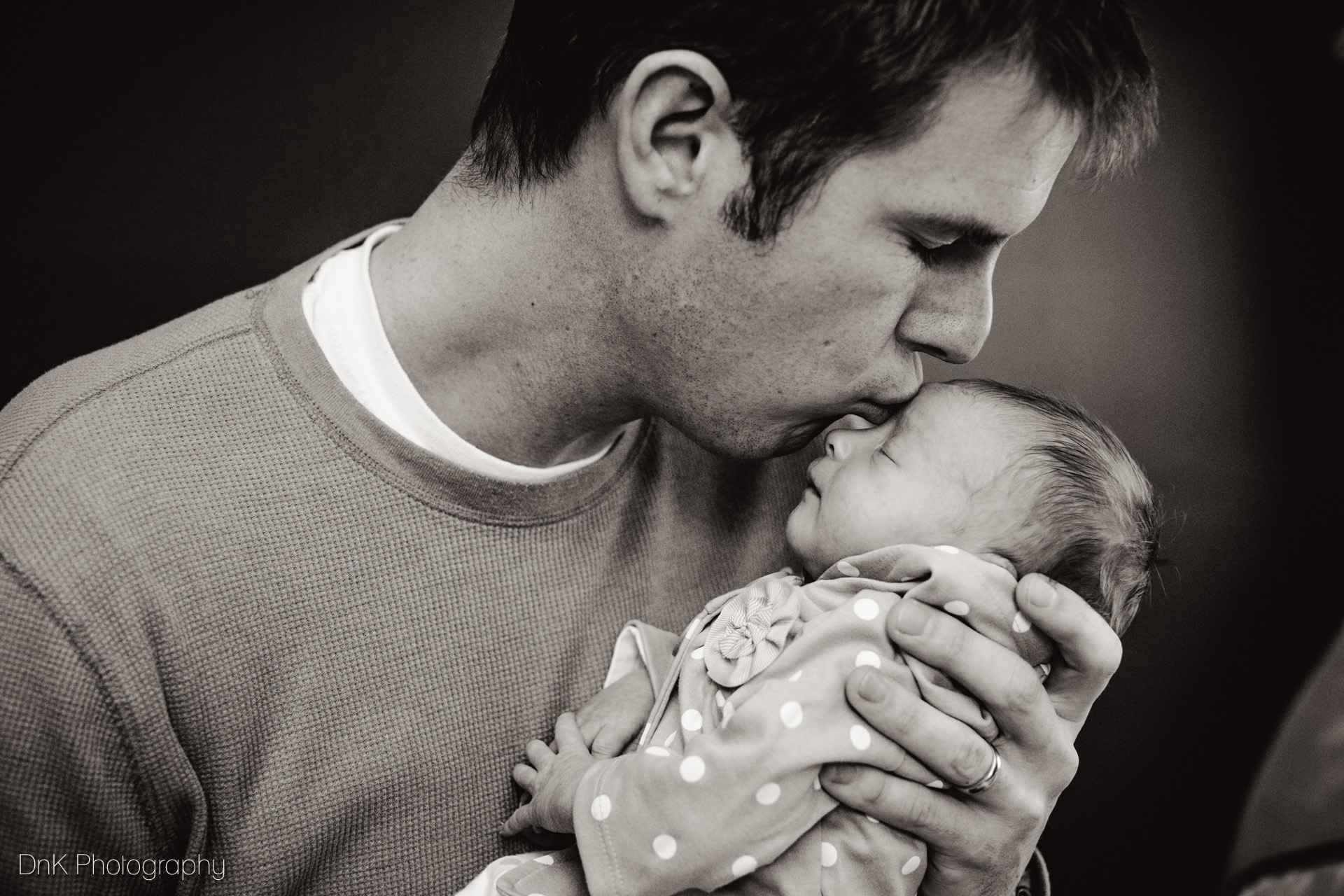 Parents love their baby father kissing his baby girl